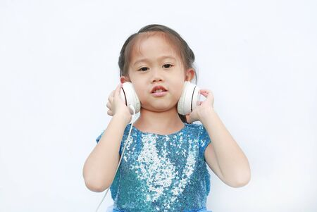 Adorable little Asian girl in bright dress listening music with headphones isolated on white background.