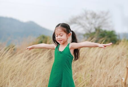 Asian Child girl with outstretched arms in the dried grass field. Rear view. Imagens