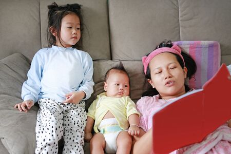 Asian mother with daughter and son read fairy tale. Female with her little children enjoying book indoors.