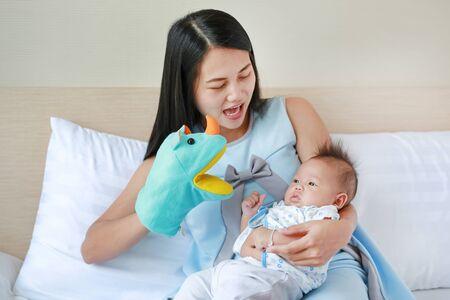 Madre jugando títeres de animales con su bebé niño en la habitación de la cama en casa. Foto de archivo
