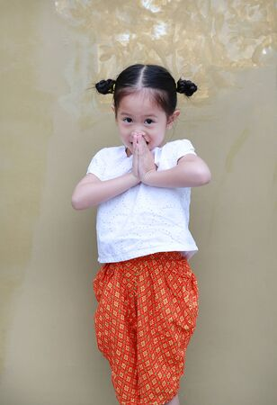 Portrait of asian child girl in traditional thai dress praying. (Sawasdee is meaning hello) Stock Photo