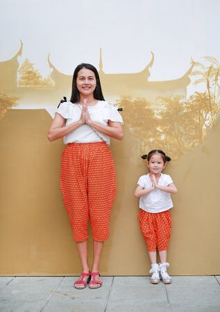 Portrait of asian mother and child girl in traditional thai dress praying. (Sawasdee is meaning hello)