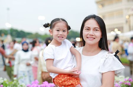 Adorable Asian child girl and mom in traditional thai dress in the public garden.