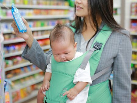 Young business woman in Convenience Store while carrying her baby boy by ergonomic baby carrier.