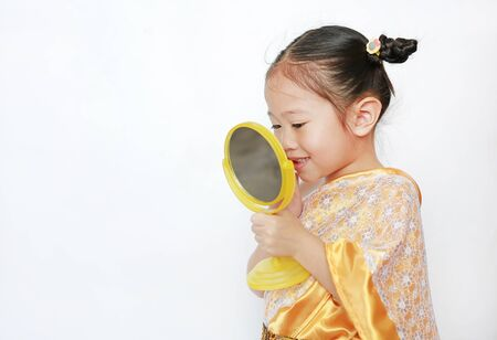 Portrait of asian child girl in traditional thai dress looking at mirror isolated on white background.
