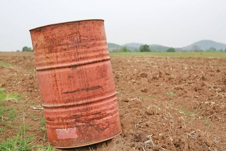An old fuel tank in summer field after harvest.