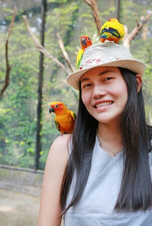 Smiling of beautiful Asian woman playing with sun conure parrots.