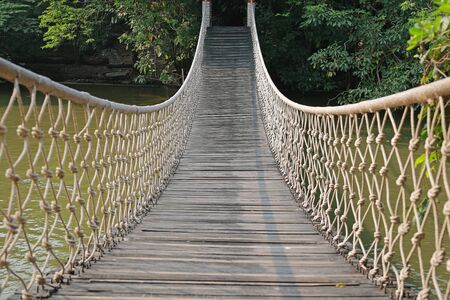Adventure wooden rope suspension bridge crossing river. Stok Fotoğraf