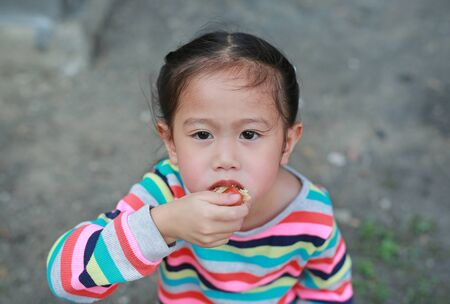 Close up Little girl eating sausage by hands outdoor. Stok Fotoğraf