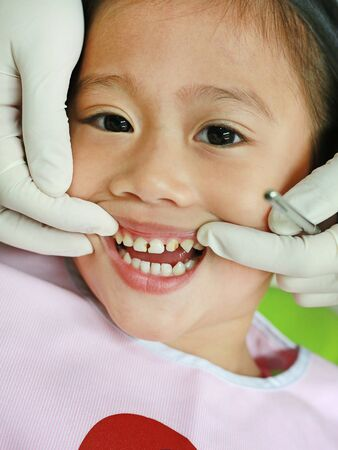 Close-up little girl during dental extraction. Child with a teeth broken and rotten.