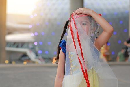 Funny face of little Asian child girl using skirt shield her face.