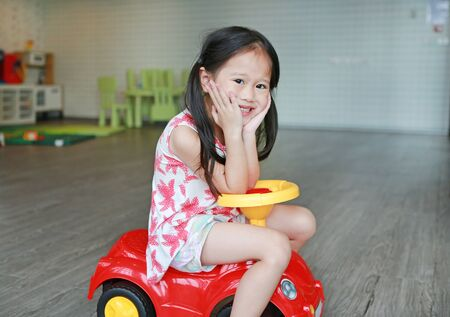 Smiling little child girl riding on a small car at playroom.