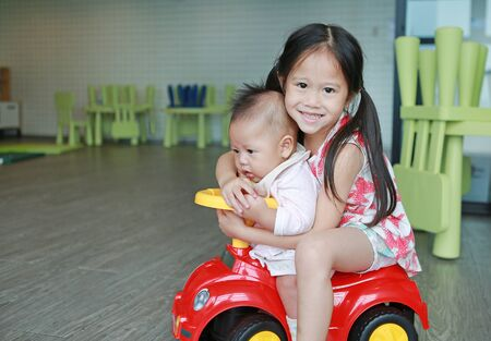 Asian Sister and little baby boy enjoying riding on a small toy car at playroom.