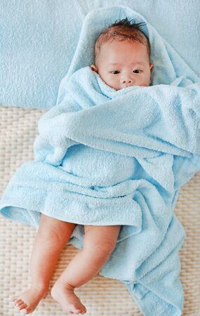 Portrait of Infant baby boy in towel roll looking at camera lying on bed after bath. Above view.