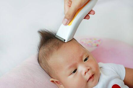 Closeup Asian infant baby boy getting a haircut. Stok Fotoğraf