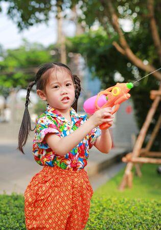 Little Asian child girl in traditional flower dress playing water gun at Songkran festival Stok Fotoğraf