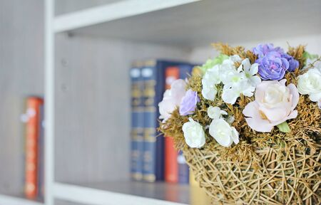 Closeup beautiful artificial rose flower in basket on the bookshelf in library.