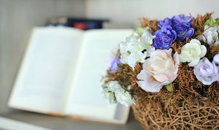 Artificial rose flower in basket on the bookshelf in library against blur of open hardcover book.
