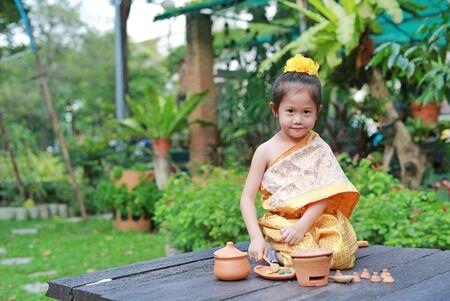 Cute Asian child girl in traditional thai dress play making Thai culture dessert in the public garden.