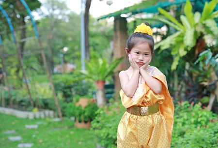 Adorable Asian child girl in traditional thai dress praying in the public garden. Stok Fotoğraf