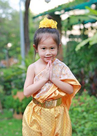 Beautiful Asian child girl in traditional thai dress praying in the public garden. Stok Fotoğraf