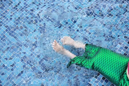 Closeup foot of little child girl wear mermaid swimming suit lying in the pool.