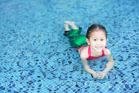Portrait of little Asian child girl in a mermaid suit sitting and lying poolside with looking camera.