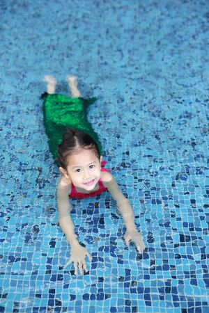 Happy little Asian child girl in a mermaid suit lying poolside with looking camera. Stok Fotoğraf