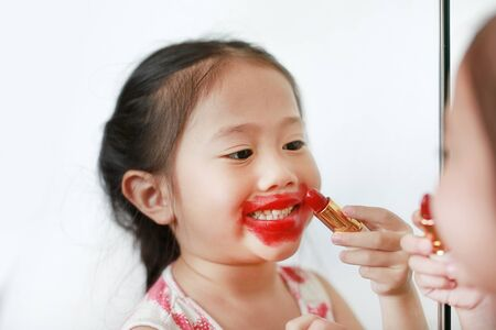 Adorable funny little girl applying lipstick over her mouth.