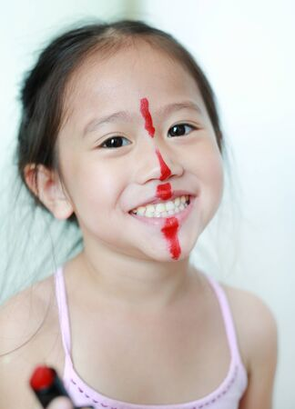 Adorable funny little girl making makeup with cosmetics. Stok Fotoğraf