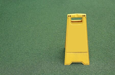 Empty yellow stand board place on artificial green grass with copy space.