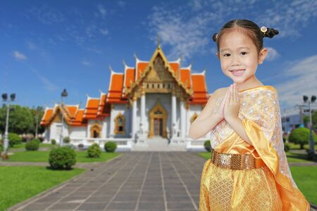 Portrait of asian child girl in traditional thai dress praying against Benjamaborphit temple in thailand.