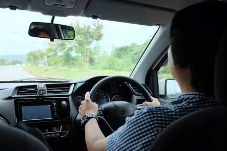 Rear view of Caucasian man in casual cloth driver holding steering wheel.