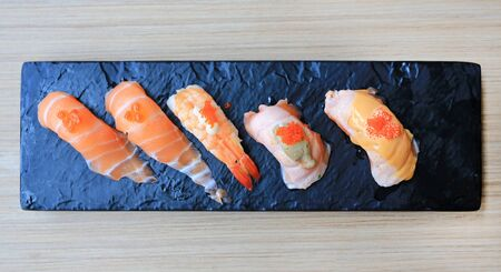 Sushi seafood set served on black stone plate on wood table. Japanese cuisine. Stock Photo - 128805354