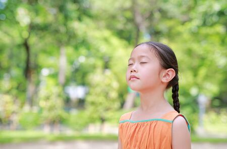 Peaceful little Asian child girl close their eyes in garden with Breathe fresh air from nature. Portrait of kid relax in green park for good health.