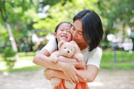 Portrait of happy Asian mother cuddle daughter and hugging teddy bear doll in the garden. Mom and child girl with love and relationship concept.
