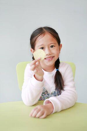 Smiling little Asian child girl eating crispy potato chips on white background. Kid enjoy eating concept.