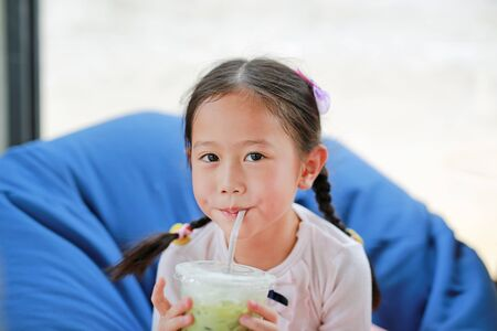 Happy little Asian child girl drinking iced Matcha Green Tea lying on sofa at cafe.