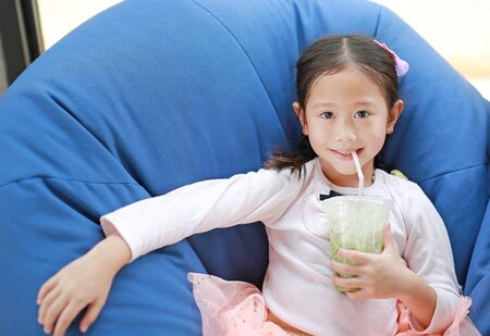 Smiling little Asian child girl drinking iced Matcha Green Tea lying on sofa at cafe. Stock Photo