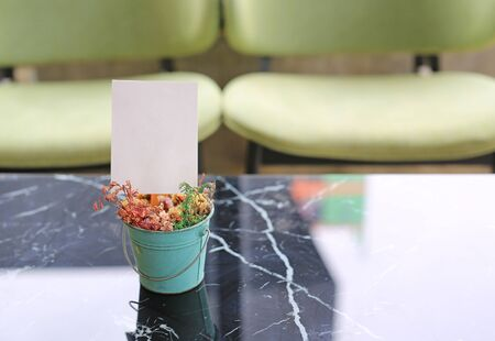 White blank paper label menu frame in mini flower pot on table at Bar restaurant.