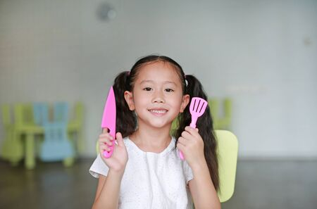 Happy little Asian child girl showing plastic knife and spade of frying pan in play room ready to cook learning.