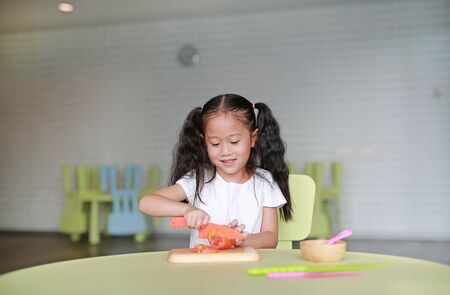 Portraits of happy Asian child girl slicing tomato vegetable on chopping board at play room. Kid play chef cooking.
