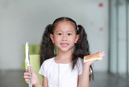 Portrait happy little child girl cooking at class room. Children show an apply strawberry jam on bread.