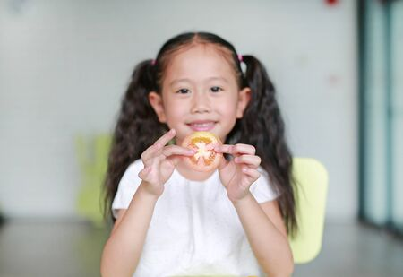 Smiling little Asian child girl holding a piece of sliced tomato. Kid eating healthy food concept. Focus at tomato in children hands.