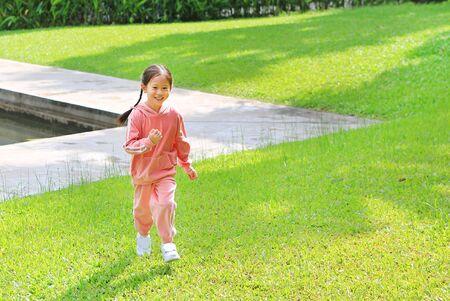 Sonriente niña niño asiático en chándal rosa corriendo en el jardín de césped verde.