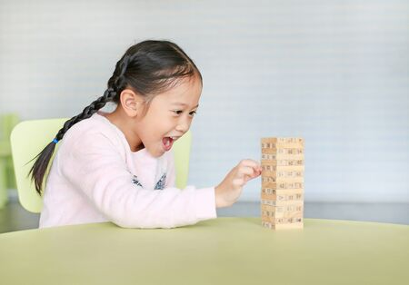 Happy little Asian child girl playing wood blocks tower game for Brain and Physical development skill in a classroom. Focus at children face. Kid imagination and learning concept. Stock Photo