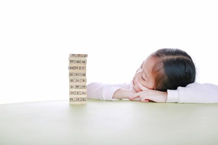 Little girl lying on table with thinking to playing wood blocks tower game for Brain and Physical development skill in a classroom. Focus at children face. Kid learning and mental skills concept. Stock Photo