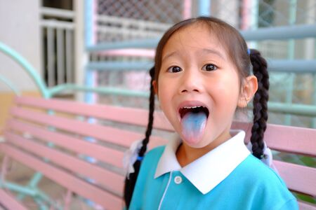 Funny face little Asian child girl smile and poking out blue colored tongue. Food coloring in children sweets. Stockfoto