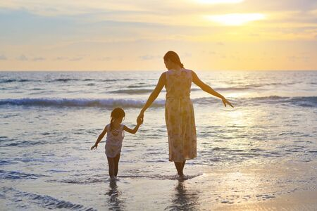 Silhouette mother and daughter playing on the beach at sunset. Stockfoto