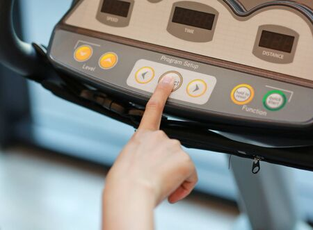 Close up of finger pushing program button on treadmill.